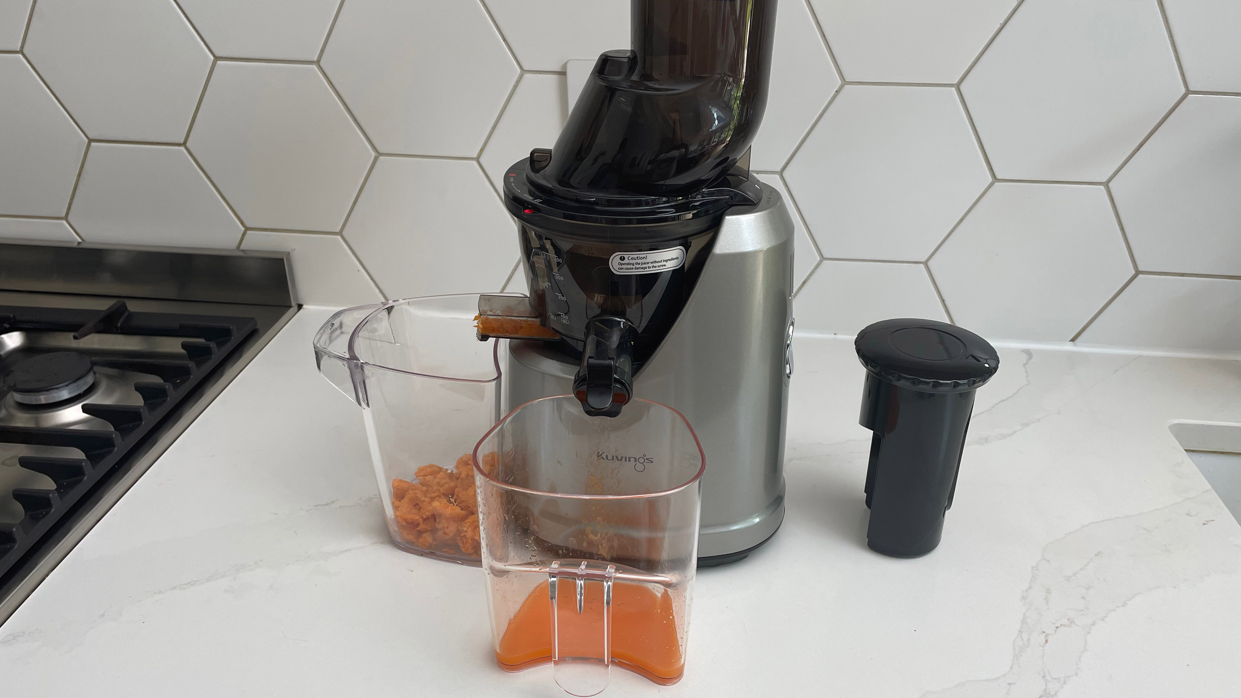 Kuvings B1700 being used to juice carrots