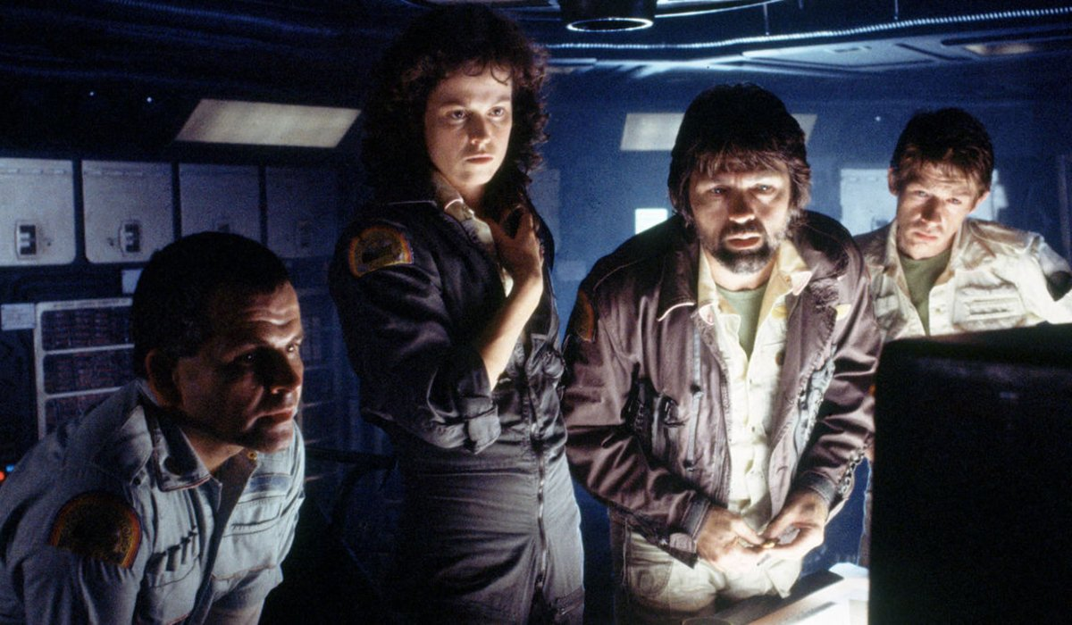 Alien Sigourney Weaver and her crewmates reading a report on screen