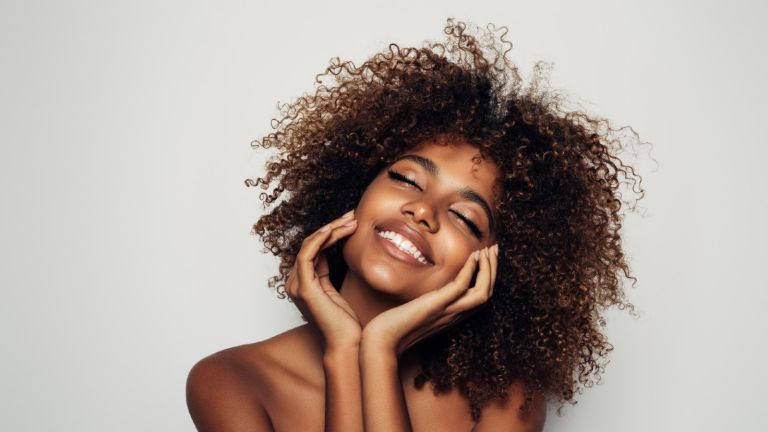 woman smiling with hands on chin