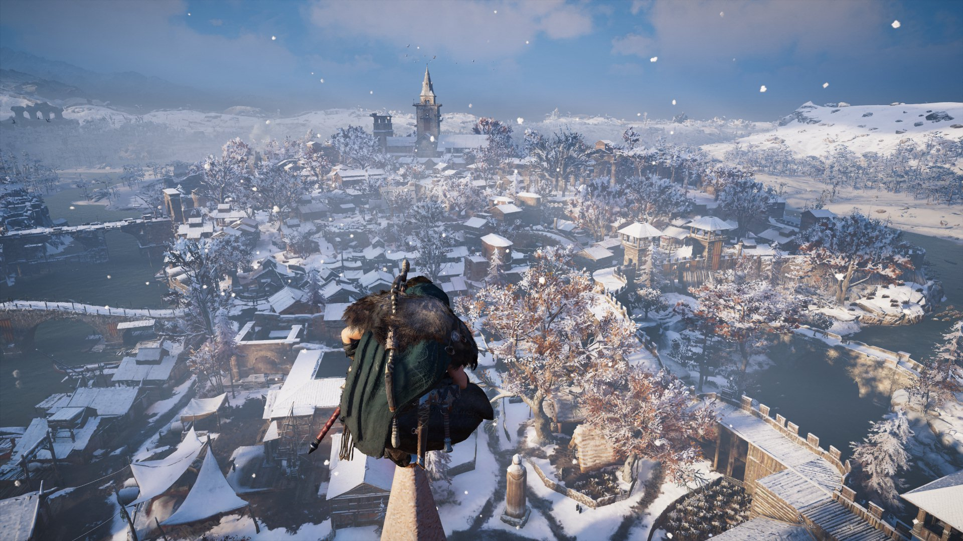 Eivor looks across a snowy town from the top of a church steeple