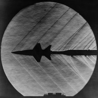 A photo taken in 1962 captures supersonic shock waves as they pass over a scale model of the American X-15 hypersonic plane.
