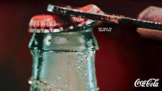 Bottle opener prizing off the cap of a Coke bottle