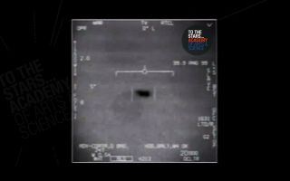 a grainy black and white video taken by the navy that shows two dark splotches that are thought to be ufos