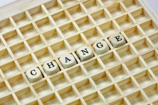 "The word ""change"" is spelled out in wooden letter cubes on a wooden grid."