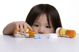 A little girl looks at blue pills on a counter.