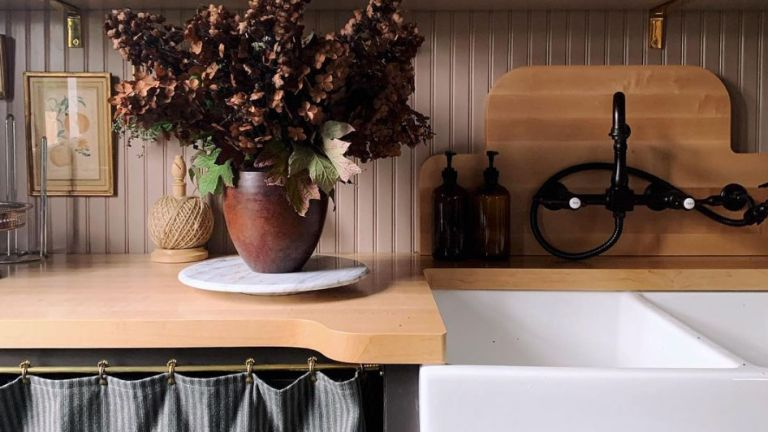 Small laundry room ideas in a brown painted wooden scheme with a jug of dried flowers beside a butler sink.