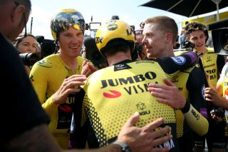Jumbo-Visma's Amund Jansen (centre) – with his number-23 squad number visible at the back of the neck of his skinsuit – celebrates winning the stage 2 team time trial and defending teammate Mike Teunissen's yellow leader's jersey at the 2019 Tour de France