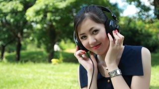 Girl listens to headphones in a tree-lined field