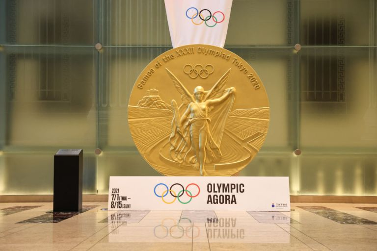 """TOKYO, JAPAN - 2021/07/21: Large-scale reproduction of Tokyo 2020 Gold Medal on display at the Olympic Agora. The Olympic Agora in Nihonbashi district is an art project which revives an ancient Greek idea of confluence of sport, art and culture. """"Agora"""" comes from Greek and stands for a vibrant public space where people gathered to buy and sell goods, exchange political ideas and do sports. (Photo by Stanislav Kogiku/SOPA Images/LightRocket via Getty Images)"""