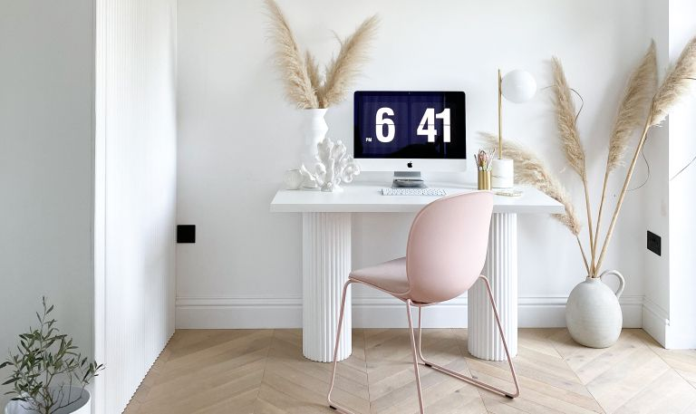 home office with a DIY desk with fluted legs and a pink desk chair and pampas grass