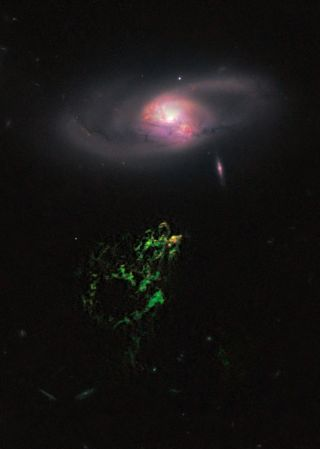 In this image by NASA's Hubble Space Telescope, an unusual, ghostly green blob of gas appears to float near a normal-looking spiral galaxy. The bizarre object, dubbed Hanny's Voorwerp (Hanny's Object in Dutch), is the only visible part of a 300,000-light-