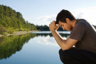 Man prays by a lake.