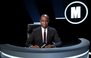 Clive Myrie sitting behind the host's desk in the Mastermind studio