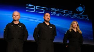 Virgin Galactic's Dave Mackay, Mike Masucci and Beth Moses on stage at the 35th Space Symposium April 9 to receive their FAA astronaut wings they earned after a Feb. 22 flight of SpaceShipTwo to the edge of space.