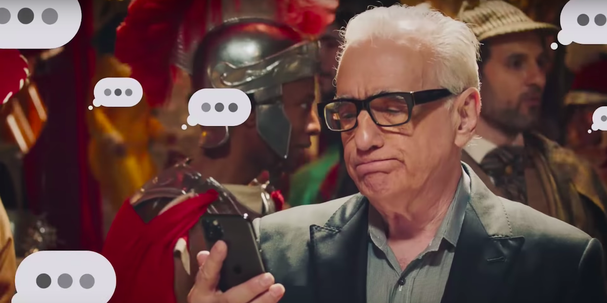 Martin Scorsese stares at his cell phone in disappointment as text message bubbles with three dots a