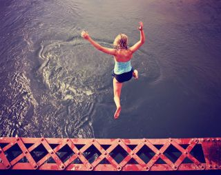 A woman leaps off a structure into water.