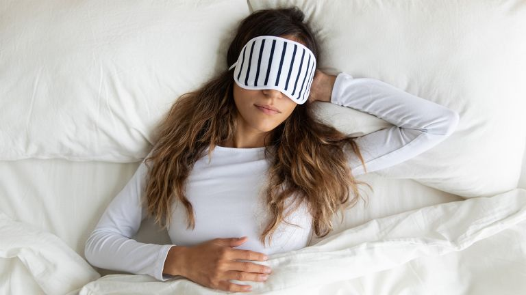 Calm peaceful young lady wearing sleeping mask, dreaming