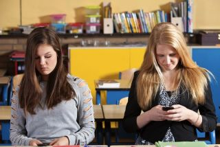 Teen girls texting in school.