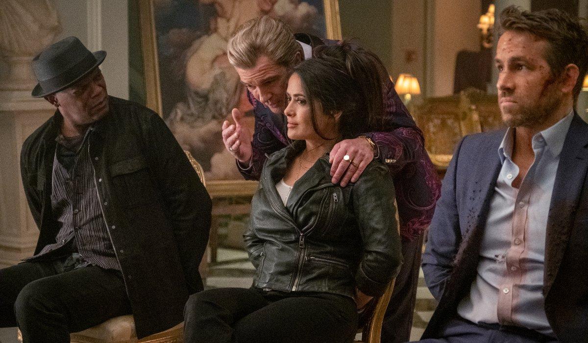 Antonio Banderas gets close to Salma Hayek, while Samuel L. Jackson and Ryan Reynolds watch in The Hitman's Wife's Bodyguard.