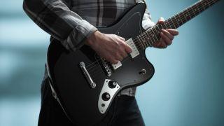 Man playing a Fender Blacktop Jaguar electric guitar