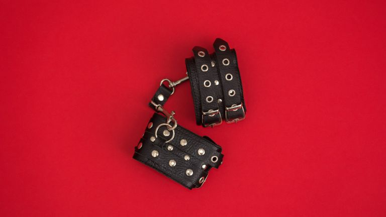 leather handcuffs on red background for BDSM for beginners