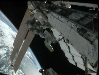 Spacewalker Akihiko Hoshide on Robotic Arm During Spacewalk