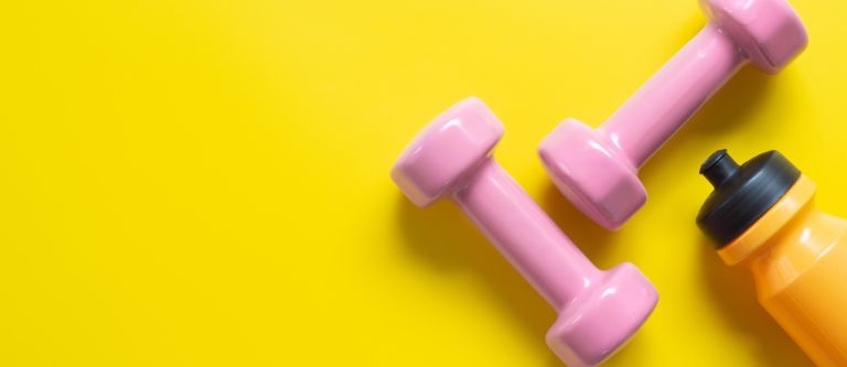 Best dumbbells for women - pink dumbbells against yellow yoga mat