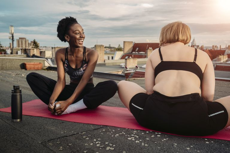 Smiling female friends exercising on rooftop, morning yoga, best time to do yoga