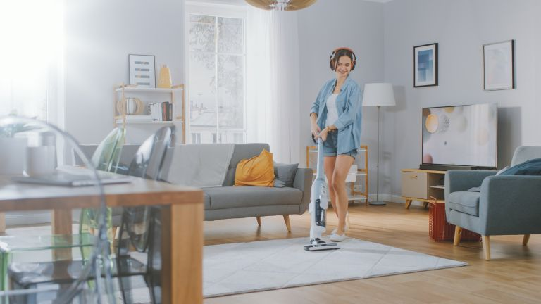 Woman with cordless vacuum cleaner