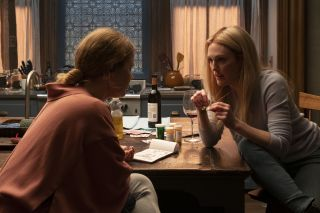 Amy Adams and Julianne Moore as Anna and Jane, sitting at Anna's kitchen table while Jane shows Anna her pendant, in The Woman In The Window