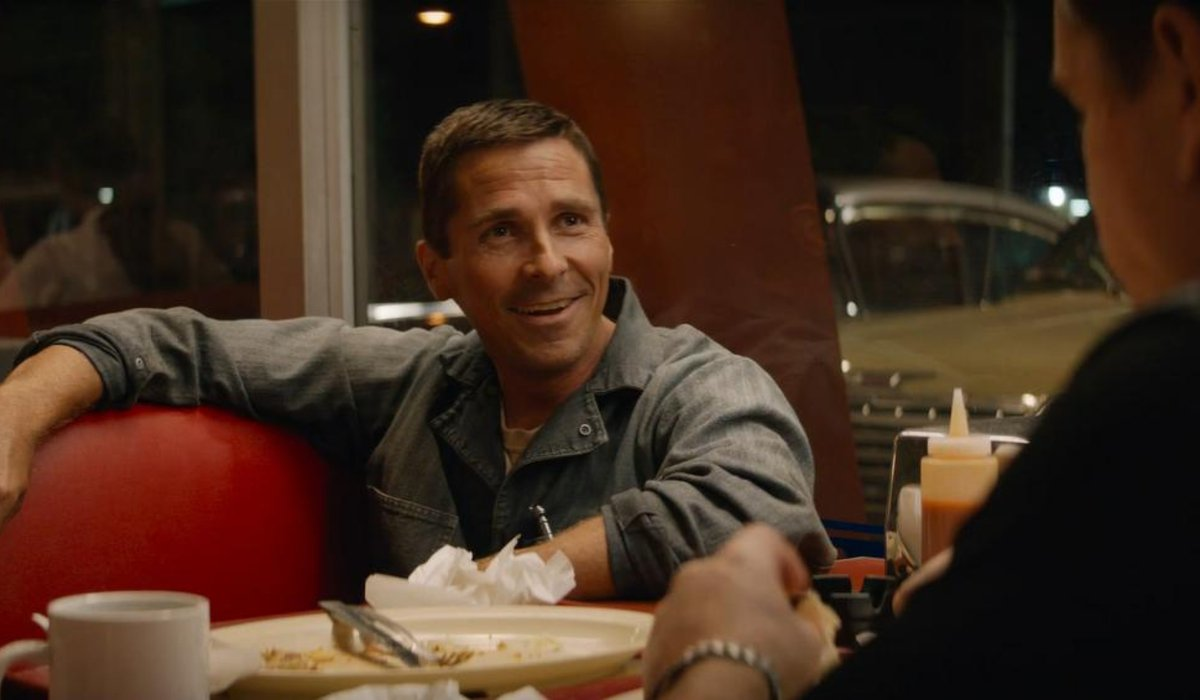 Ford V. Ferrari Christian Bale smiles in front of a cluttered diner table