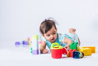A baby plays with colorful toys.