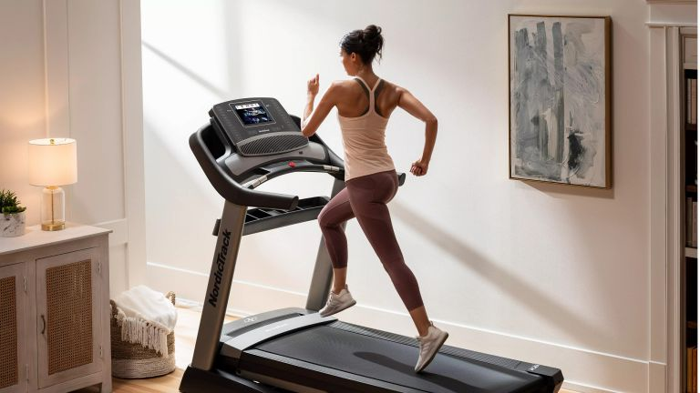 Person running on a NordicTrack Commercial 1750 folding treadmill in a living room