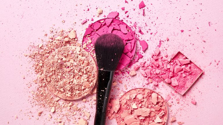 Crushed face powders and makeup brush on pink background