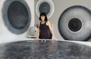 Artist Carol Prusa surrounded by her astronomy-inspired silverpoint artwork.