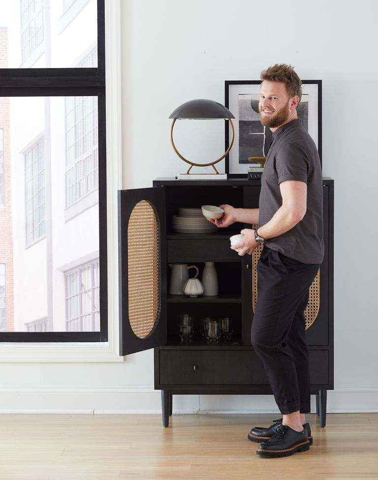 Bobby Berk in front of black and white cabinet
