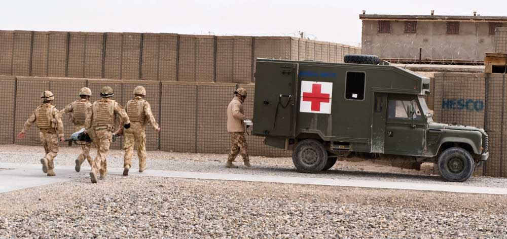 Image of army medics transporting a patient into back of an army truck with red cross logo on the side