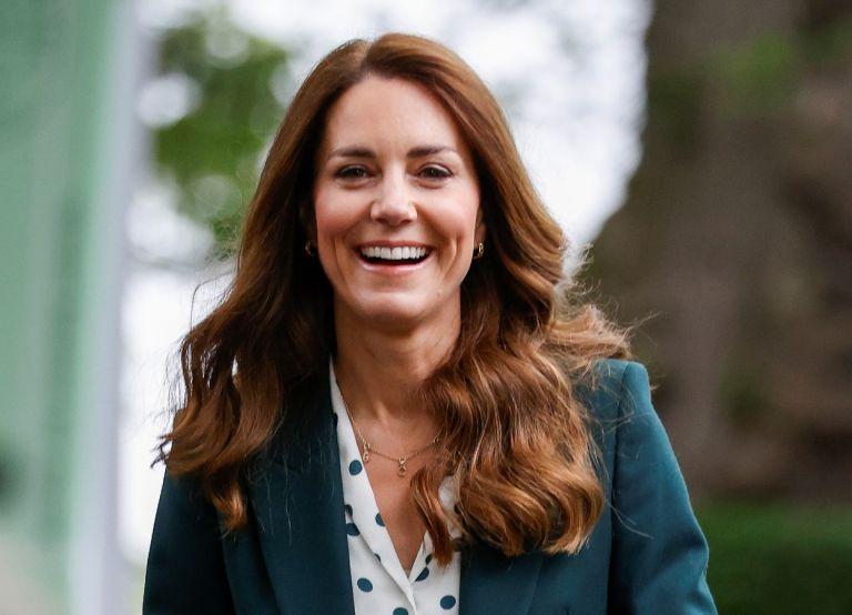 Kate Middleton smiling wearing a green jacket