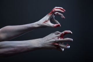 Blood-stained zombie hands reach out.