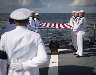 U.S. Navy Lieutenant Commander Paul Nagy, USS Philippine Sea, and Carol Armstrong, wife of Neil Armstrong, commit the cremated remains of Neil Armstrong to sea during a burial at sea service held onboard the USS Philippine Sea (CG 58), Friday, Sept. 14, 2
