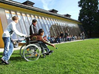 Other students watch as boy in wheelchair plays lawn game.