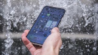 An iPhone getting drenched with water
