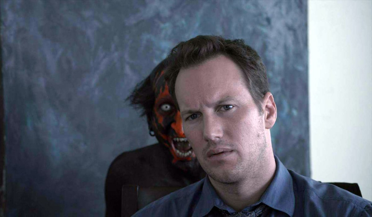Something creepy stands behind Patrick Wilson in Insidious.