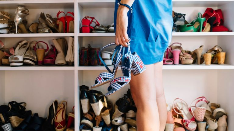 Woman with shoes in the hand and women's shoes in the rack.