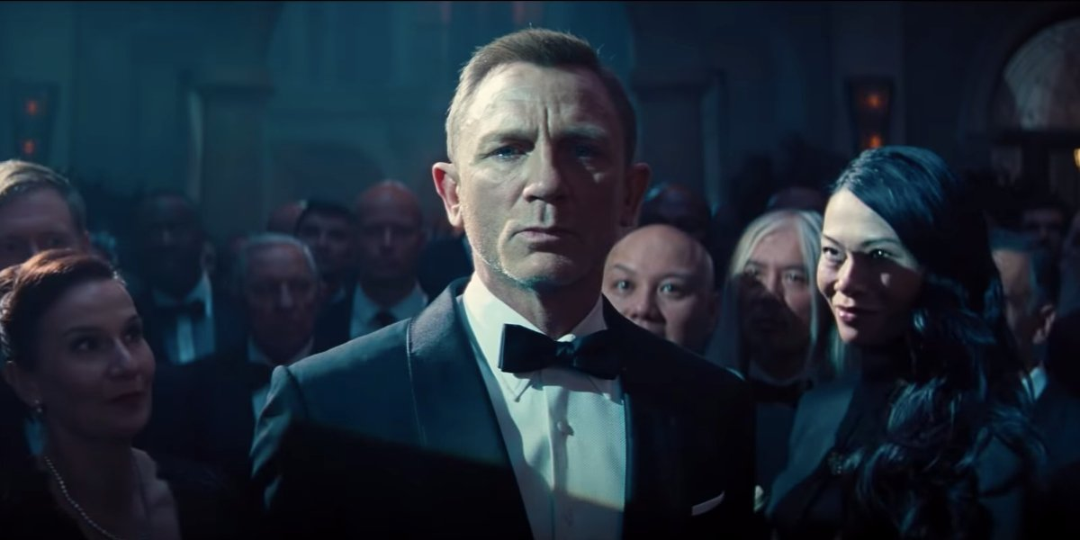 No Time To Die Daniel Craig surrounded by staring strangers