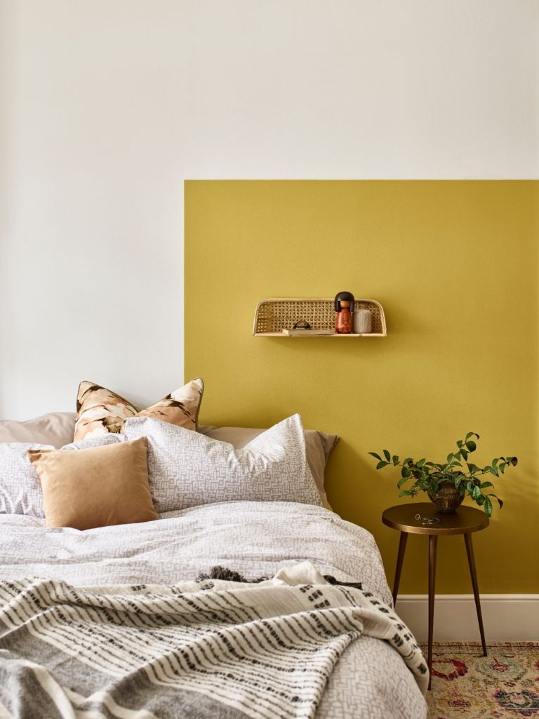Yellow painted wall behind bed with wall light and soft furnishings