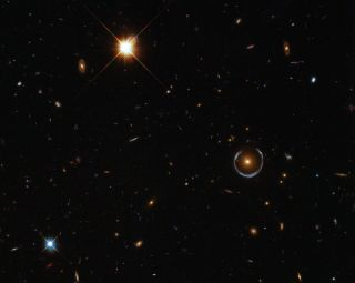 This image shows an Einstein ring (middle right), which occurs when a massive object acts like a lens for light coming toward the observer from a background object.