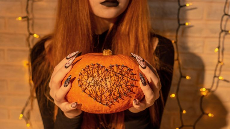 Halloween Nail Art Design, hands and pumpkin decorated with nails and threads close up.