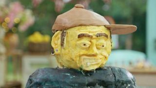 A yellow cake version of Tom Delonge grimaces hauntingly at the camera