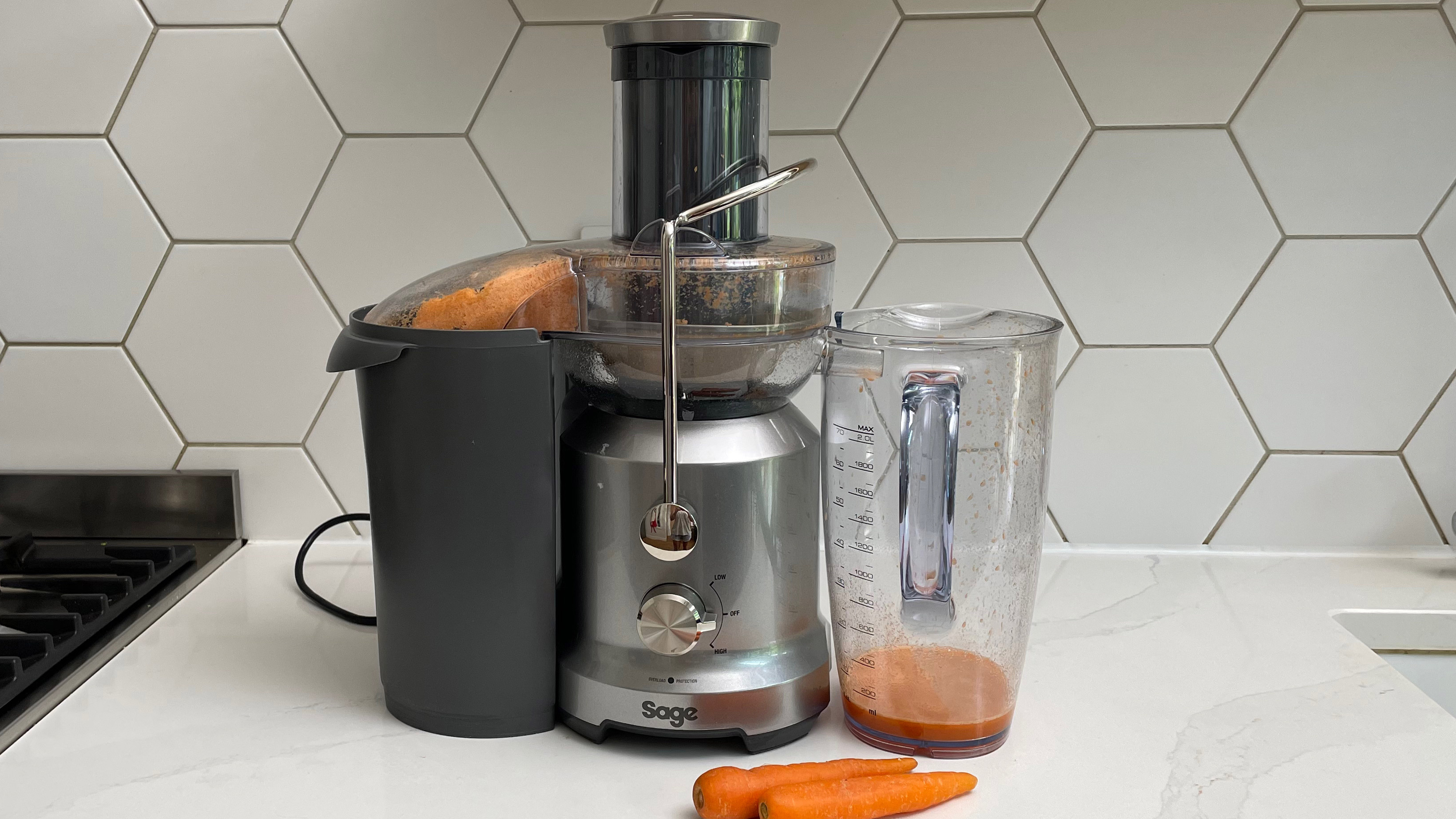 Breville the Juice Fountain Cold on a kitchen countertop filled with carrot juice